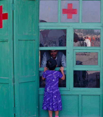 child and man at a red cross station