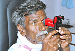 Man in India self-administering an eye exam using a NETRA wireless device
